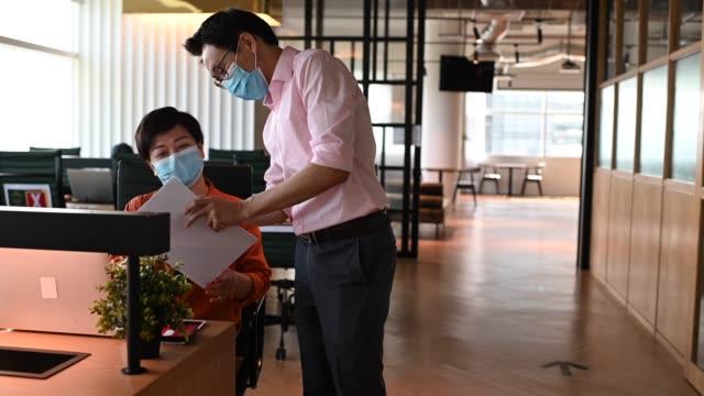 vídeos y material grabado en eventos de stock de 2 colega chino asiático saludando el uno al otro con nuevo estilo de apretón de manos en la oficina con máscara protectora en - codo