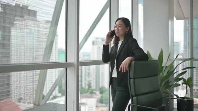 アジアの中国の自信ホワイトカラーの女性は、窓の横にある彼女のオフィスで携帯電話で聞いて話しています - white collar worker点の映像素材/bロール