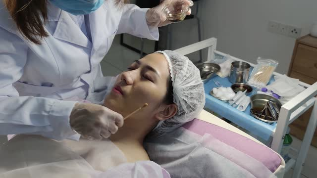 asian chinese cosmetologist is applying moisturizing on client face. woman skin procedure. natural cosmetic products. facial treatment. - clostridium botulinum stock videos & royalty-free footage