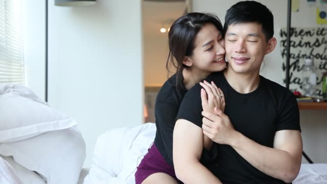 asian chinese couple hugging each other having bonding time on bed in the morning - tan stock videos and b-roll footage