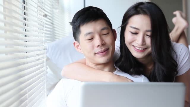 asian chinese couple in bedroom surfing internet with laptop having bonding time together - tan stock videos and b-roll footage