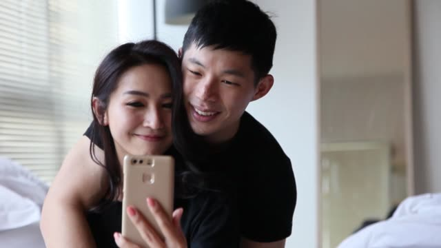 asian chinese couple on bed shooting selfie with their mobile phone camera having fun and bonding time in the morning - tan stock videos and b-roll footage