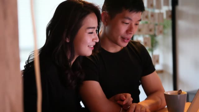 asian chinese couple surfing internet using laptop in living room and talking to each other - tan stock videos and b-roll footage