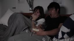 asian chinese couple watching movies while eating popcorn at home
