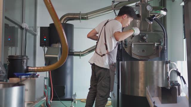 コーヒーロースター焙煎生コーヒー豆からコーヒー豆を抽出するトリーアを抱いて微笑むアジアの中国の職人は、焙煎の進行状況をチェックする香り - 人間の鼻点の映像素材/bロール