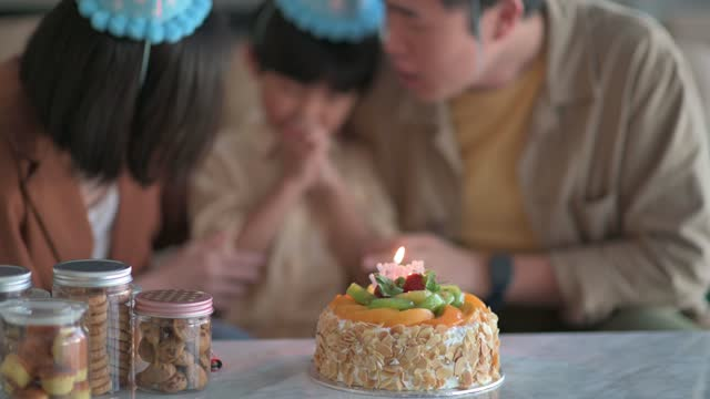 asian chinese family at home celebrating birthday with son wearing party hat singing, clapping and wishing in front of birthday cake - party hat stock videos & royalty-free footage
