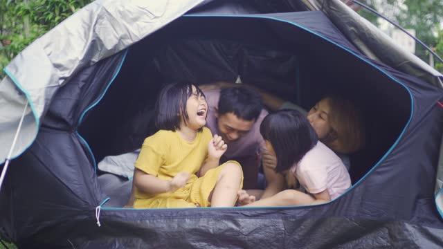 vidéos et rushes de camping asiatique de famille chinoise à l'arrière-cour de leurs activités de week-end de staycation de maison - famille avec deux enfants