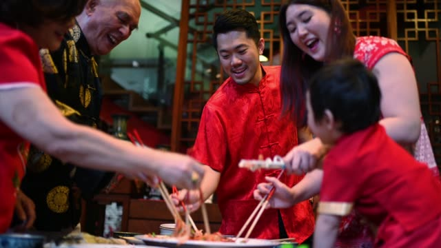 asian chinese family chinese new year reunion dinner having traditional dishes raw fish lau sang - chinese culture stock videos & royalty-free footage