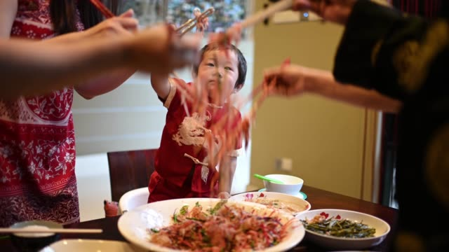 asian chinese family chinese new year reunion dinner having traditional dishes raw fish lau sang - malaysian culture stock videos & royalty-free footage