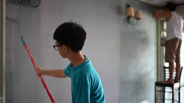 asian chinese family members painting their house son helping his father - diy stock videos & royalty-free footage