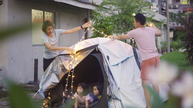 vidéos et rushes de famille chinoise asiatique mettant sur la lumière de corde décorant le camping à l'arrière-cour de leurs activités de week-end de staycation de maison - activité de plein air