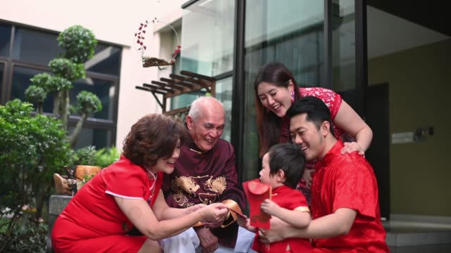 asian chinese family senior grandparent giving red packet ang pao to grandson after chinese new year reunion dinner having traditional dishes raw fish lau sang - prosperity stock videos & royalty-free footage