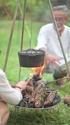 asian chinese family with 2 adult offspring setting up campfire and getting ready to cook for their meal