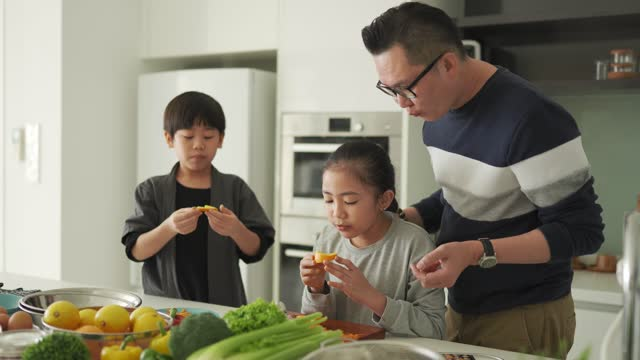 asian chinese father and daughter cutting oranges and eating together with son in kitchen counter - ascorbic acid stock videos & royalty-free footage