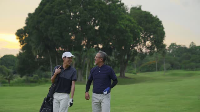 asian chinese father and son golfers walking and having good conversation and smiling at golf course during sunset - country club stock videos & royalty-free footage