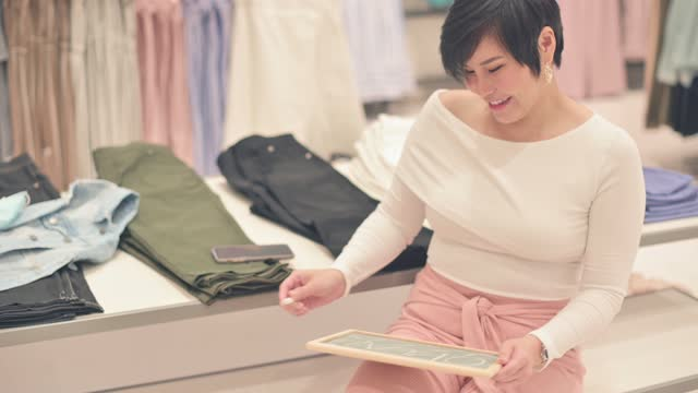 朝に開いた言葉で黒板黒板にチョークの書き込みを使用してアジアの中国の女性ブティック衣料品店の店主 - 1日目点の映像素材/bロール