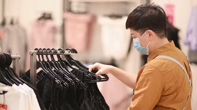 アジアの中国の女性ブティック店の衣料品店のオーナーが服を手配する - ハンガー点の映像素材/bロール