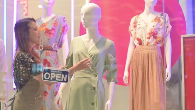 アジアの中国の女性ブティック店のオーナーは、ビジネスの準備を午前中に開くために近い看板を回す - 1日目点の映像素材/bロール