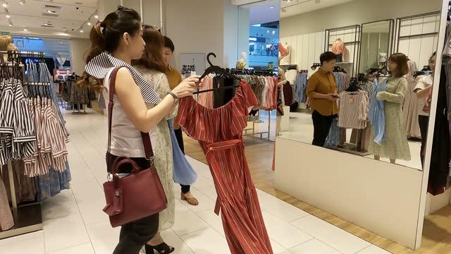 アジアの中国人女性は、鏡を見て衣料品店で服を選ぶ - mirror点の映像素材/bロール