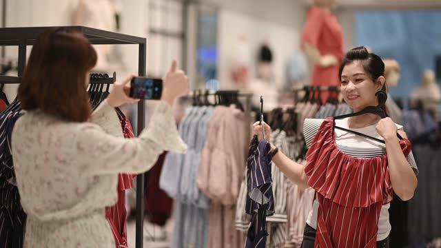 vídeos de stock e filmes b-roll de asian chinese female choosing clothes at clothing store - amizade feminina