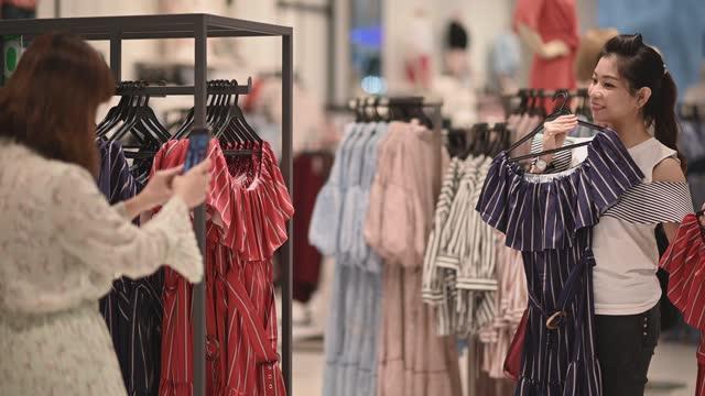 stockvideo's en b-roll-footage met aziatische chinese vrouw die kleren bij kledingopslag kiest - winkeldisplay