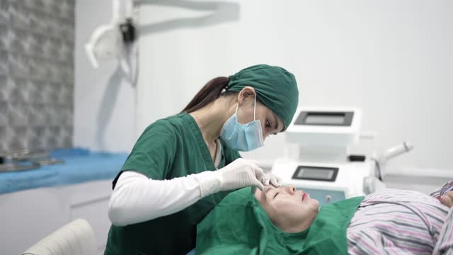 asian chinese female doctor injecting female patient on her forehead with botulinum (botox). - clostridium botulinum stock videos & royalty-free footage