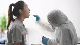asian chinese female doctor with PPE taking mouth swab from patient Coronavirus test. Medical worker in protective suite taking a swab for corona virus test, potentially infected woman