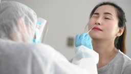 asian chinese female doctor with PPE taking nasal swab from patient Coronavirus test. Medical worker in protective suite taking a swab for corona virus test, potentially infected woman