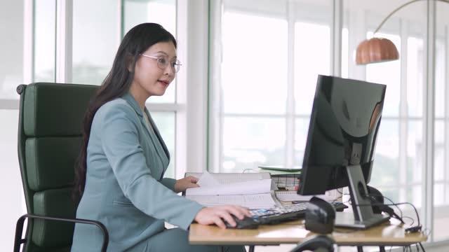 デスクトップpcの前で働く彼女のオフィスに座ってアジアの中国の女性の幹部管理 - 最高経営責任者点の映像素材/bロール