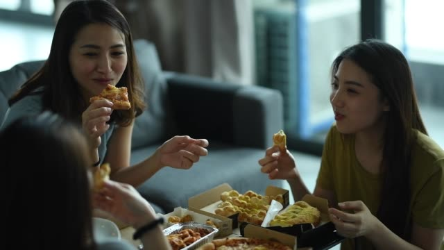 3 asian chinese female friends having pizza for lunch in their living room bonding time - female friendship stock videos & royalty-free footage