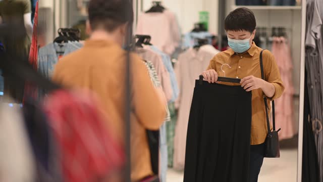 アジアの中国の女性の手はドレスを持って、衣料品店で笑顔で鏡を見て - 鏡点の映像素材/bロール