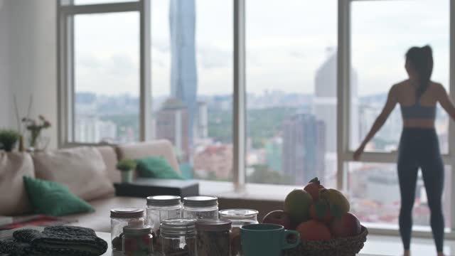 asiatische chinesische weibliche haus-workout im häuslichen wohnzimmer mit blick auf die stadt - menschliche gliedmaßen stock-videos und b-roll-filmmaterial