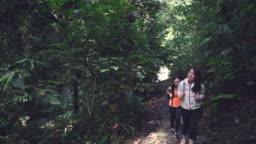 2 asian chinese female sisters walking uphill talking in jungle trekking