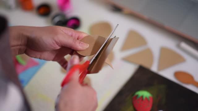 vídeos de stock, filmes e b-roll de professora chinesa asiática cortando com tesoura durante aula de arte online em casa - desenhar atividade