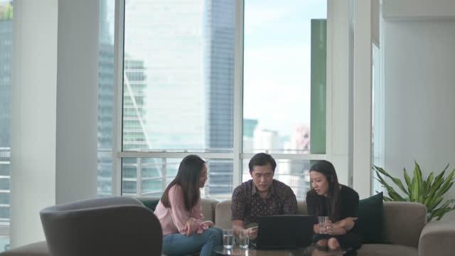 アジアの中国人の友人の同僚は、ラップトップとの結合時間を持つロビーラウンジのソファに座っています - 玄関ホール点の映像素材/bロール