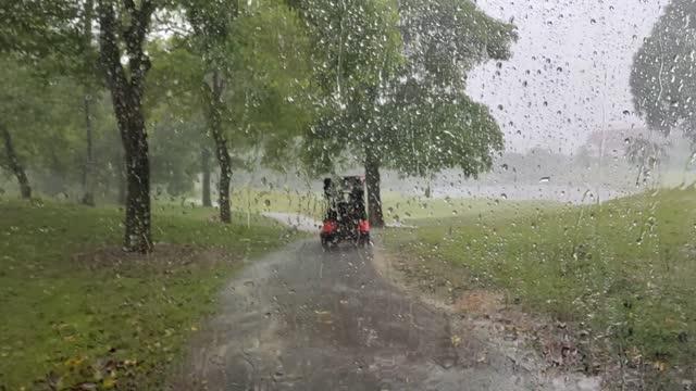 gruppo asiatico cinese di golfisti e famiglie che guidano golf cart e passano attraverso un vialetto allagato durante la giornata di pioggia al campo da golf - irriducibilità video stock e b–roll
