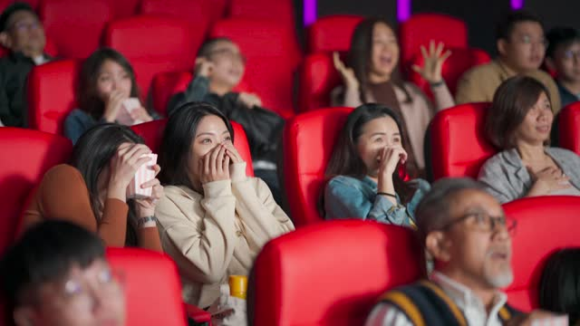 asian chinese  group of people watching horror scary movie in cinema movie theatre covering face - shock stock videos & royalty-free footage