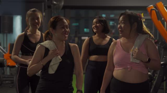 楽しいトレーニングの後、ジムのヘルスクラブから出て行く女性のアジアの中国のグループ - 女性選手点の映像素材/bロール
