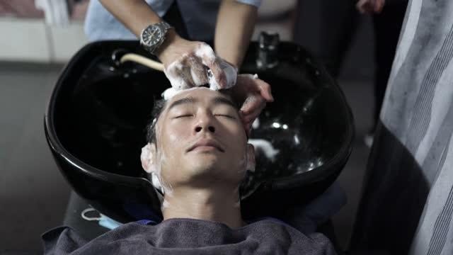 asiatische chinesische friseur waschen haare für seinen kunden in haar-salon - körperpflege stock-videos und b-roll-filmmaterial
