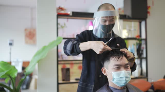 vídeos de stock e filmes b-roll de asian chinese hairstylist with protective workwear cutting hair for his customer in hair saloon - estilo de cabelo