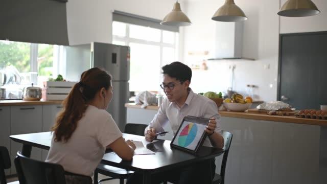 vídeos y material grabado en eventos de stock de agente de seguros chino asiático explicando a sus clientes en la cocina sobre las pólizas - oficio de ventas