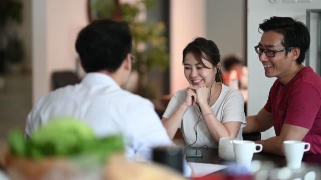 vídeos de stock, filmes e b-roll de agente de seguros chinês asiático explicando a seus clientes na cozinha sobre as apólices - etnia oriental