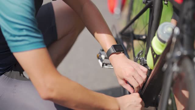 アジアの中国人男性サイクリストは、農村シーンの道路側でロードバイクチェーンを固定 - クロスカントリーサイクリング点の映像素材/bロール