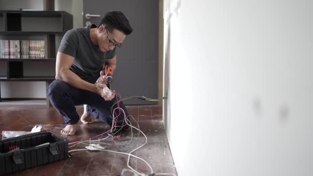 stockvideo's en b-roll-footage met aziatische chinese mannelijke elektricien verbindt de stopcontacten met de elektrische draden. installatiedraad in een stekker. - cable
