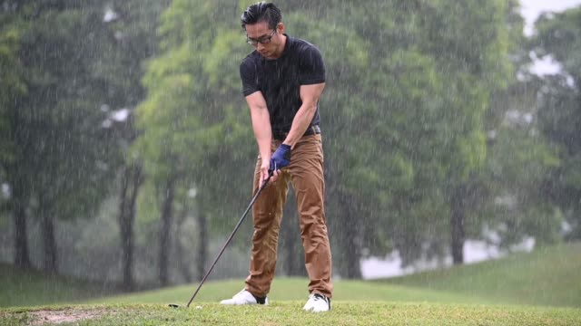 asian chinese male golfer playing golf in the rain in melaka alone wet - male likeness stock videos & royalty-free footage