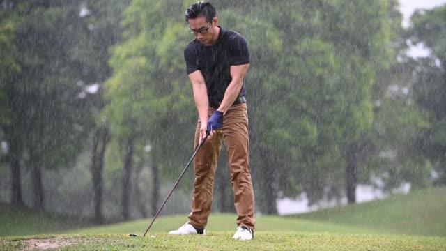 asiatiska kinesiska manliga golfare spelar golf i regnet i melaka ensam våt - golf bildbanksvideor och videomaterial från bakom kulisserna