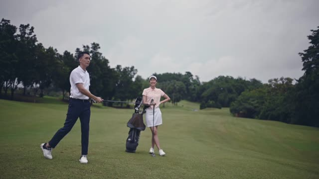 asian chinese male golfer teeing off and swing his driver club on the golf course - golf swing stock videos & royalty-free footage