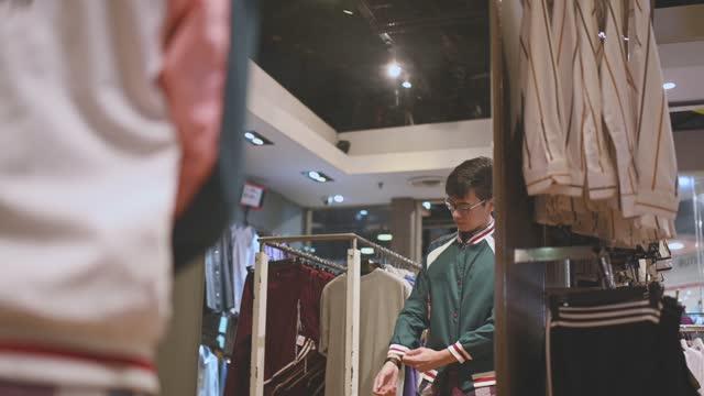アジアの中国の男性の手は、右の1つの買い物を選択しようとしている衣料品店でメンズウェアシャツを持っています - 店頭点の映像素材/bロール