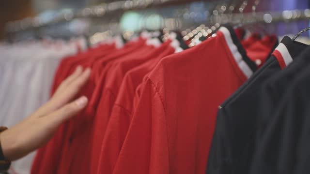 アジアの中国の男性の手は、右の1の買い物を選択する衣料品店でメンズウェアシャツを持っています - ハンガー点の映像素材/bロール