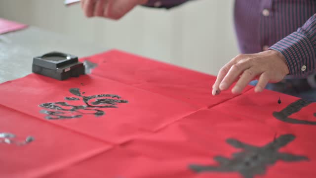 asian chinese male practising chinese caligraphy for coming chinese new year celebration home decoration purpose with prosperity and good wording by writing it on a red piece of paper - hobbies stock videos & royalty-free footage